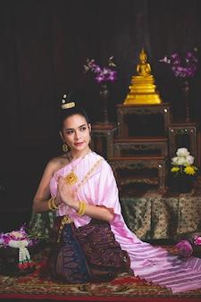 Bella donna asiatica, thailandesi indossava un abito tailandese retrò rosa e riposava le mani nella stanza di preghiera.
