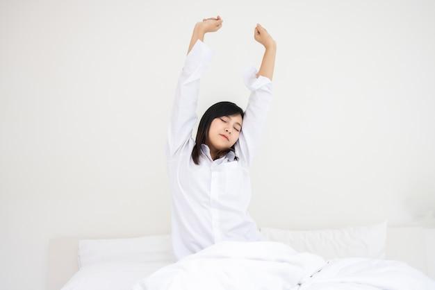La bella donna asiatica si sveglia la mattina