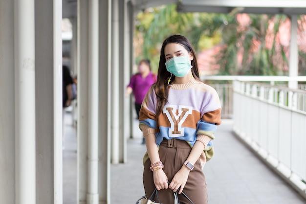 La bella donna asiatica che cammina in città indossa maschere mediche in un nuovo concetto normale