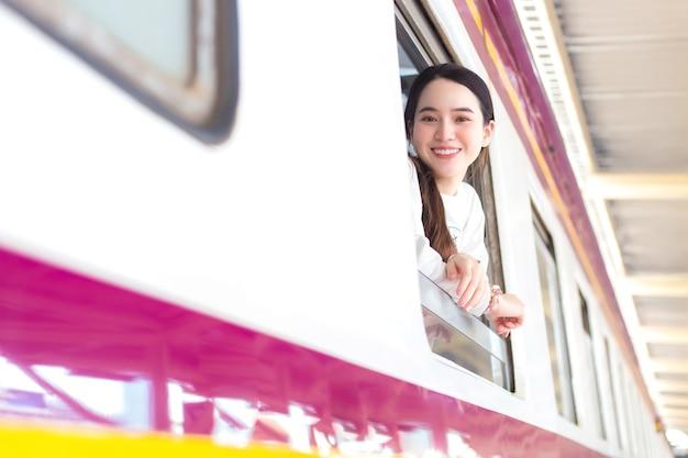 Una bella donna asiatica che indossa un camice bianco vicino alla finestra ha detto ciao ciao alla sua famiglia a causa del lavoro in città in treno o arriva e saluta a casa alla stazione.