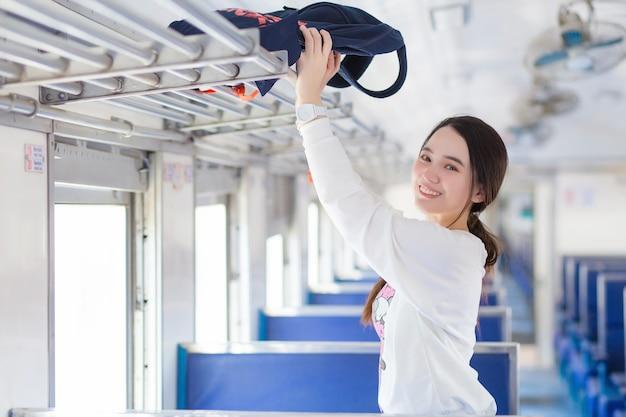 La bella donna asiatica in camicia bianca sta viaggiando in treno il giorno di vacanza mentre tiene la borsa