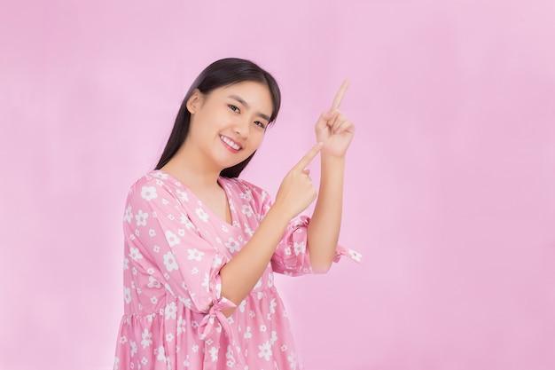 La bella donna asiatica con capelli lunghi neri in camicia rosa mostra il punto della mano in su per presentare qualcosa