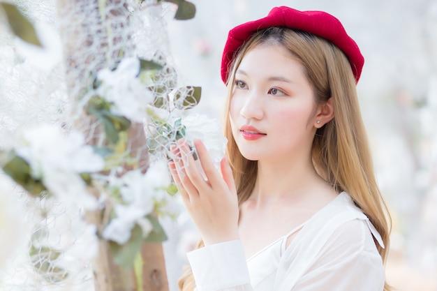 La bella giovane signora asiatica sta cercando un fiore bianco nel giardino naturale.