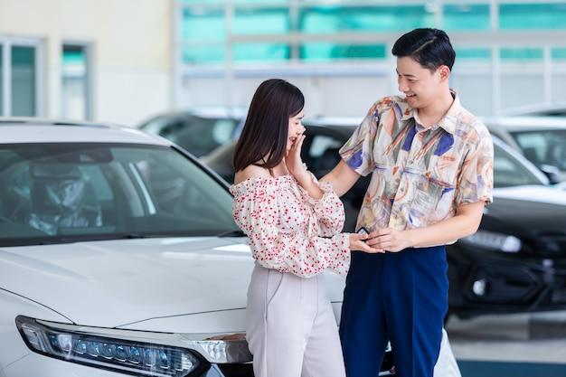 Belle giovani coppie sorridenti asiatiche che tengono una chiave della loro nuova automobile nella stanza di manifestazione.