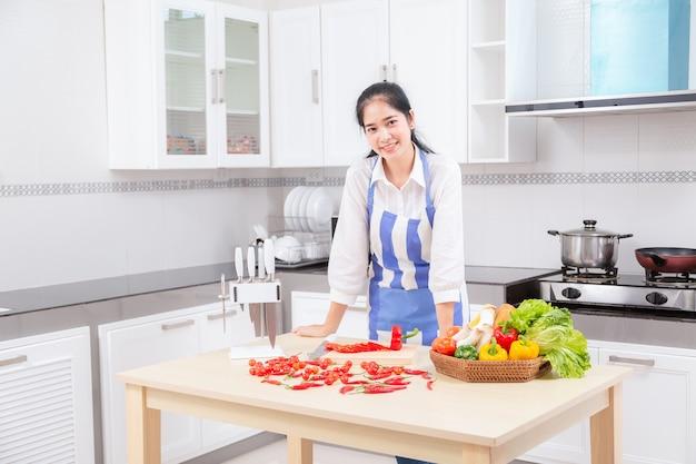 La bella giovane donna asiatica in cuoco sta mescolando la pastella.
