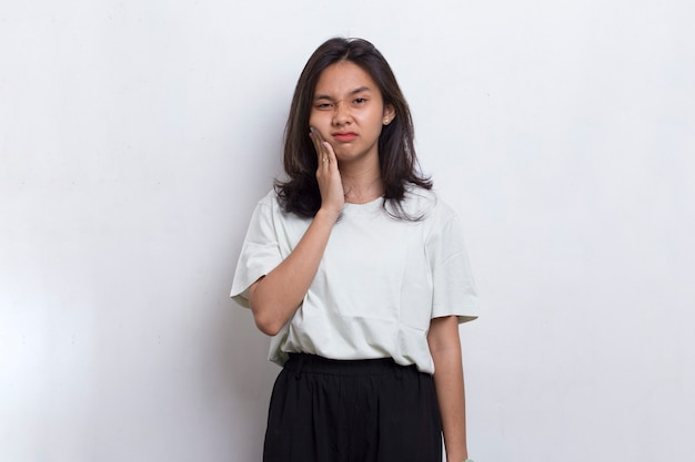 Bella giovane donna asiatica che soffre di mal di denti, dolore, carie, sensibilità ai denti