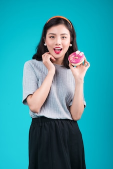 Ragazza asiatica di bellezza che tiene ciambella rosa. retro donna gioiosa con dolci, dessert in piedi su sfondo blu.