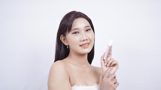 Bellezza asiatica che mostra rossetto in mano isolata su sfondo bianco