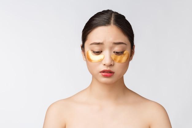 La donna asiatica dell'adolescente di bellezza si preoccupa della sua pelle con le toppe delle maschere di occhio dell'oro sotto gli occhi con preoccupazione.