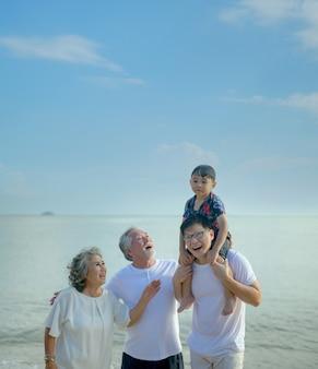 La grande famiglia asiatica viaggia insieme sulla spiaggia. età pensionabile con figlio e nipote relax e svago durante le vacanze estive.