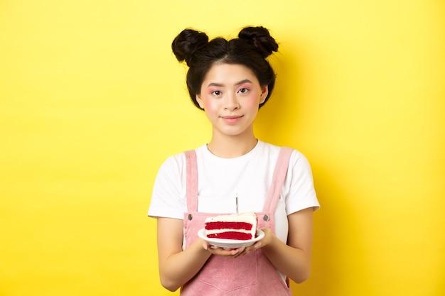 Ragazza asiatica di compleanno in piedi con la torta e sorridente, celebrando il b-day su giallo.