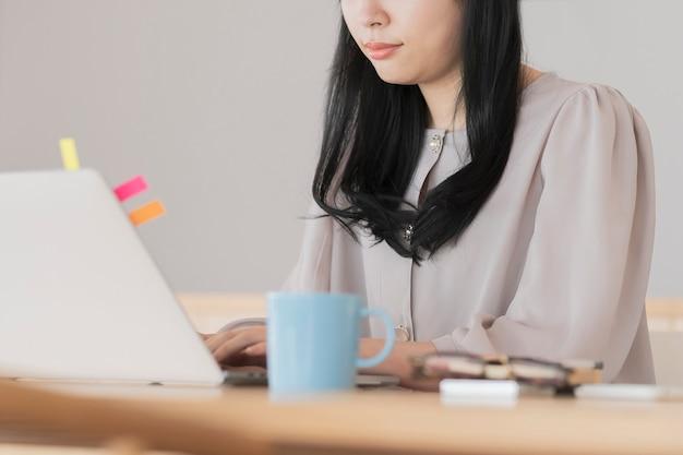 Donna dai capelli neri asiatica che lavora da casa utilizzando un computer portatile