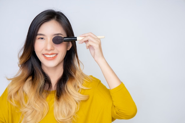 Una blogger asiatica di bellezza che gira un video in cui indossa un rossetto arancione in uno studio.