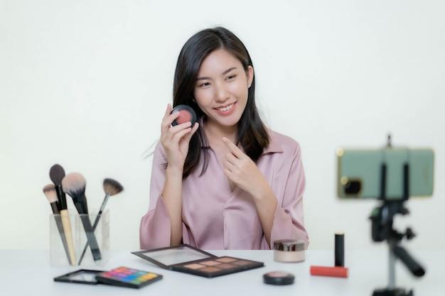 Una beauty blogger blogger asiatica che gira un video in cui indossa un rossetto arancione in uno studio.