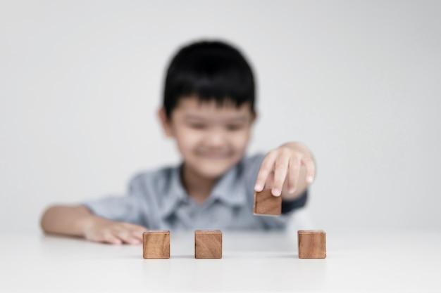 Ragazzo asiatico che sceglie cubi di legno, concetti educativi e impara in una nuova normalità.