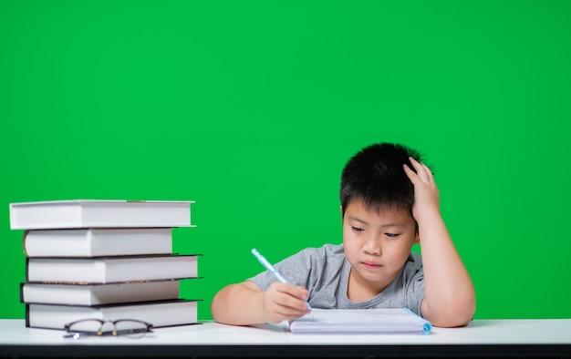 Ragazzo asiatico che fa i compiti sullo schermo verde, carta da lettere del bambino, concetto di istruzione, torna a scuola