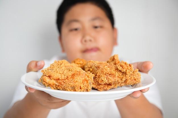 Il ragazzo asiatico mangia il pollo fritto