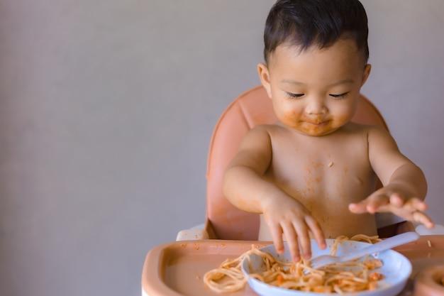 Ragazzo asiatico che eatting sull'alta sedia del bambino