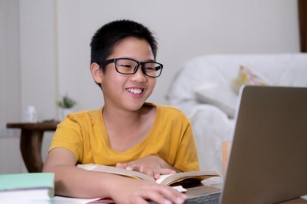 Il ragazzo asiatico gode dello studio autonomo con l'e-learning a casa