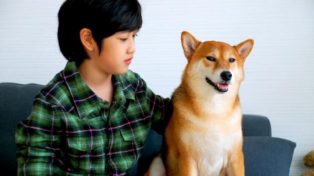 Ragazzo asiatico divertendosi a giocare con il suo cane sul divano di casa.