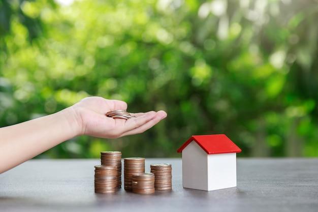 Pila asiatica dei soldi e della moneta della tenuta del ragazzo con il modello della casa su verde.