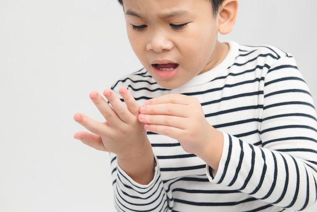 Il ragazzo asiatico tiene la mano nell'altra mano ha un graffio e scorre nel sangue che gli fa male