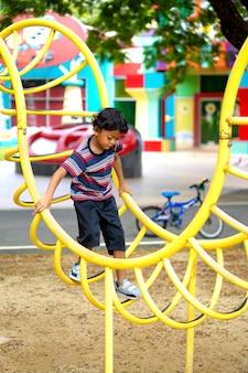 Un ragazzo asiatico si sta arrampicando su un parco giochi in una scuola.