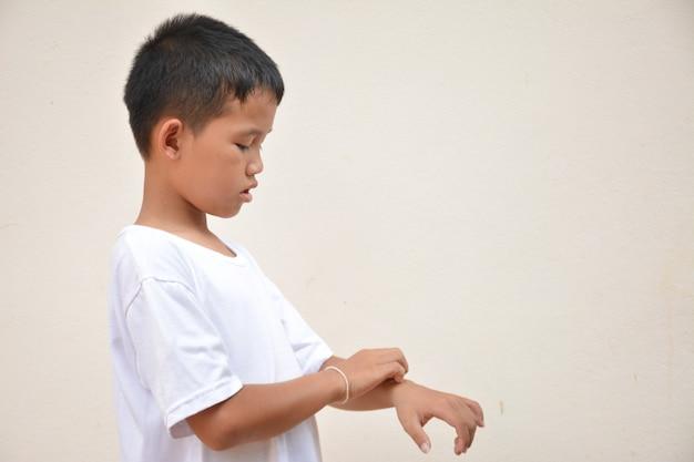 Pelle pruriginosa del ragazzo asiatico