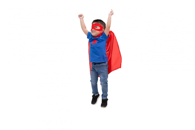 Ragazzo asiatico che salta con il piccolo potere divertente dell'eroe isolato sulla parete bianca, concetto del supereroe