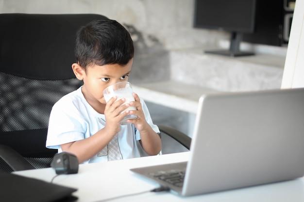 Ragazzo asiatico bambino seduto a tavola con il computer portatile e si prepara a scuola. concetto di formazione online. studio della lezione di lezione di videoconferenza online.