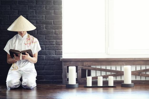 Monaco ragazzo asiatico in kimono che legge un vecchio libro