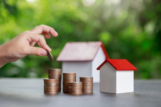 Ragazzo asiatico che mette soldi per coniare pila con il modello della casa su verde.