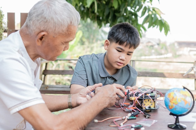 Ragazzo asiatico e nonno in pensione apprendimento del processo di programmazione della nuova tecnologia robotica