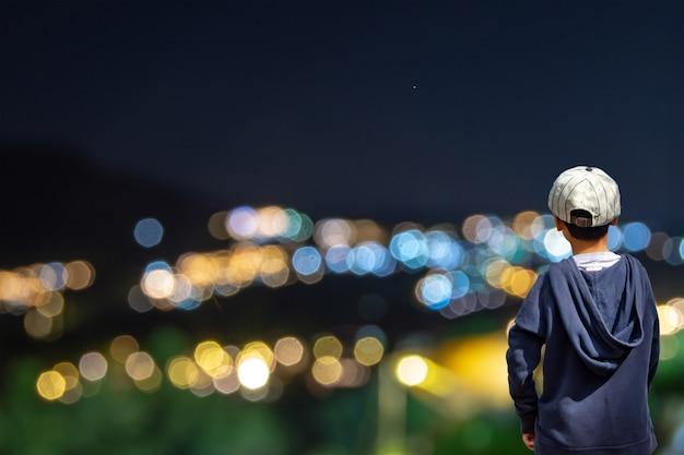 Il ragazzo asiatico vede luci sfocate delle case sulla montagna.