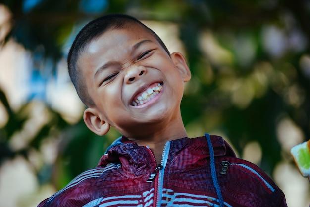 Ragazzo asiatico che sorride con la priorità bassa della natura