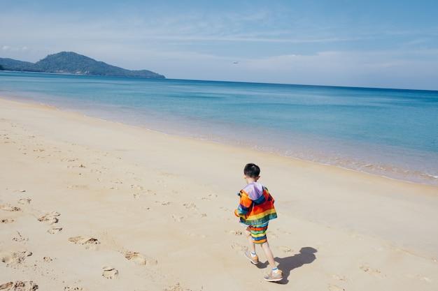 Ragazzo asiatico che cammina sulla spiaggia all'aperto mare e cielo blu