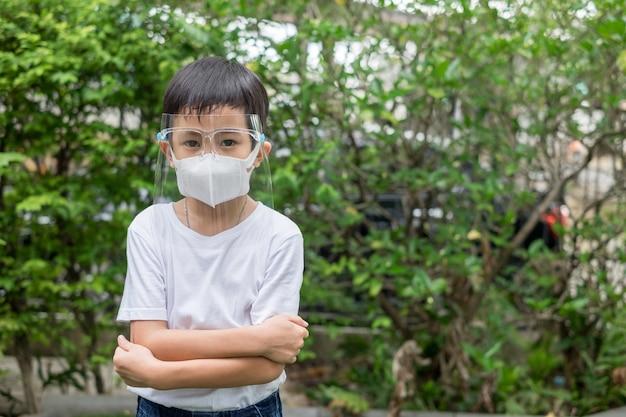 Ragazzo asiatico indossare maschera e schermo facciale nel giardino di casa