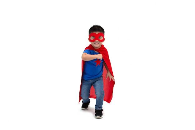 Ragazzo asiatico con piccolo potere divertente dell'eroe isolato su fondo bianco, concetto del supereroe