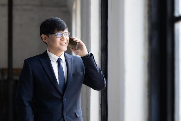 Gli affari asiatici in occhiali stanno sulla finestra usano lo smartphone per effettuare chiamate di affari, uomo d'affari in abito formale che sorride usando lo smartphone.
