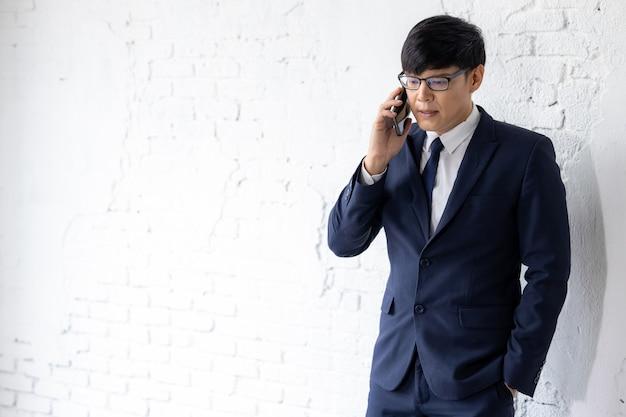 Affari asiatici in occhiali si erge su sfondo bianco muro utilizza smart phone per effettuare chiamate aziendali, uomo d'affari che lavora utilizzando smart phone.