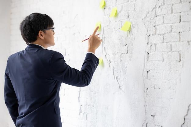 Gli affari asiatici in occhiali stanno sulla finestra usano il programma di promemoria della carta per appunti appiccicosi per discutere l'idea in ufficio, l'uomo d'affari che guarda e pensa il blocco note nel muro bianco.