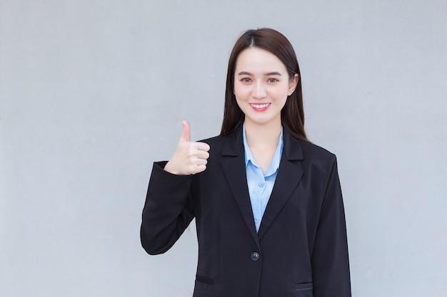 Una donna d'affari asiatica che indossa un abito nero sorride e mostra il colpo di mano come segno di