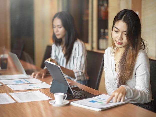 Lavoratrici asiatiche d'affari che concentrano il loro lavoro nella stanza dell'ufficio con relazione finanziaria, laptop e tazza di caffè