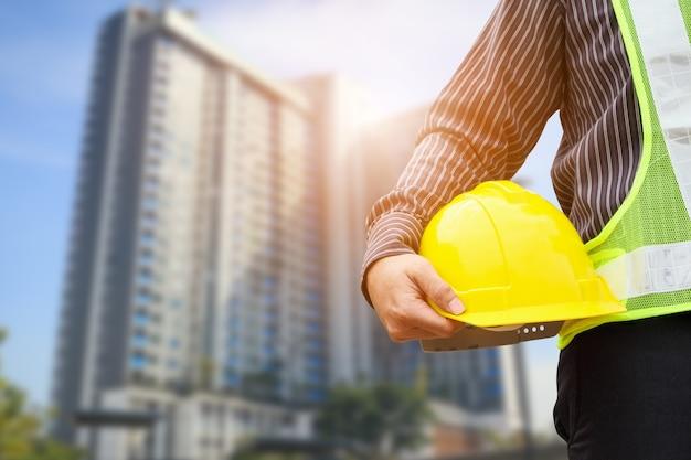 Lavoratore asiatico dell'ingegnere o dell'architetto della costruzione dell'uomo di affari con il casco protettivo giallo al grande cantiere del condominio