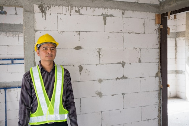 Lavoratore asiatico dell'ingegnere di costruzione dell'uomo di affari nel casco protettivo e carta dei modelli a disposizione al cantiere della casa