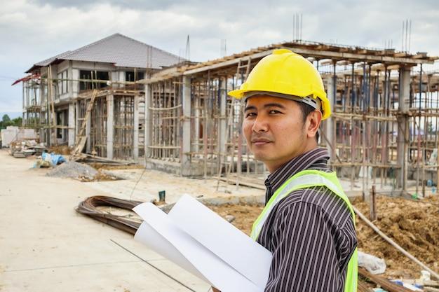 Uomo d'affari asiatico ingegnere edile lavoratore in casco protettivo e carta dei progetti a portata di mano al cantiere della casa