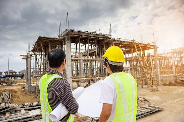 Il direttore di costruzione asiatico dell'uomo di affari e il lavoratore dell'ingegnere in casco protettivo tengono la carta dei modelli a disposizione al cantiere della casa