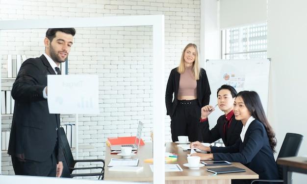 L'uomo d'affari asiatico e la donna del collega guardano il responsabile caucasico che dà la presentazione sul posto di lavoro.
