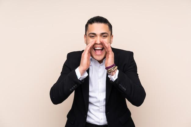 Uomo d'affari asiatico isolato su sfondo beige che grida con la bocca spalancata