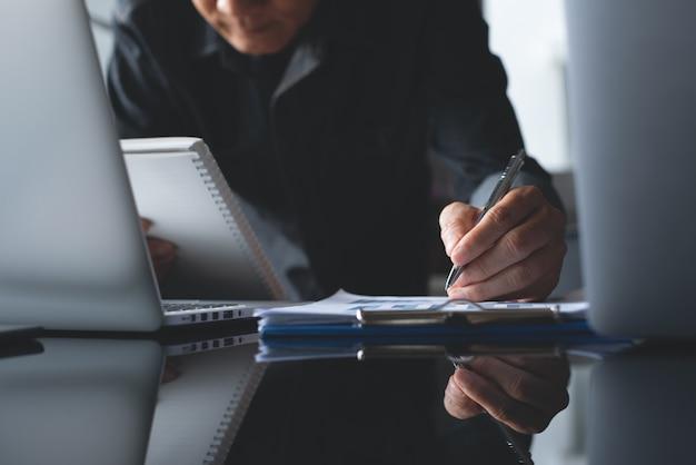 Uomo d'affari asiatico che esamina il rapporto sui dati di vendita